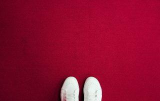 zapatillas blancas sobre fondo rojo